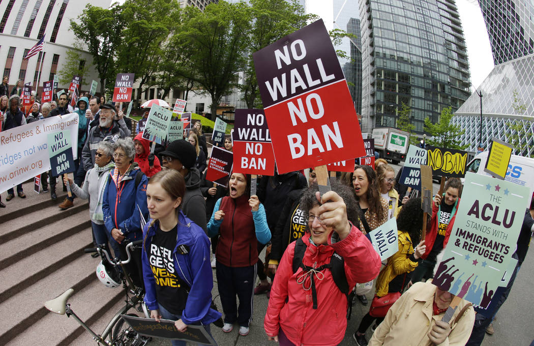 Protesters wave signs and chant during a demonstration against President Donald Trump's revised travel ban outside a federal courthouse in Seattle on May 15, 2017. 9th U.S. Circuit Court of Appeal ...