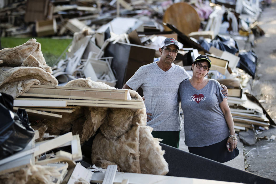 Steve and Sherri Blatt pose for a photograph on Wednesday amongst the debris near their home in the aftermath of Hurricane Harvey in Houston. Harvey's record-setting rains now have the potential t ...