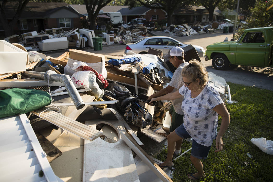 Blatt helps his neighbor Tamlyn Lima collect golf clubs from debris piled in front of her home Wednesday in the aftermath of Hurricane Harvey in Houston. Harvey's record-setting rains now have the ...