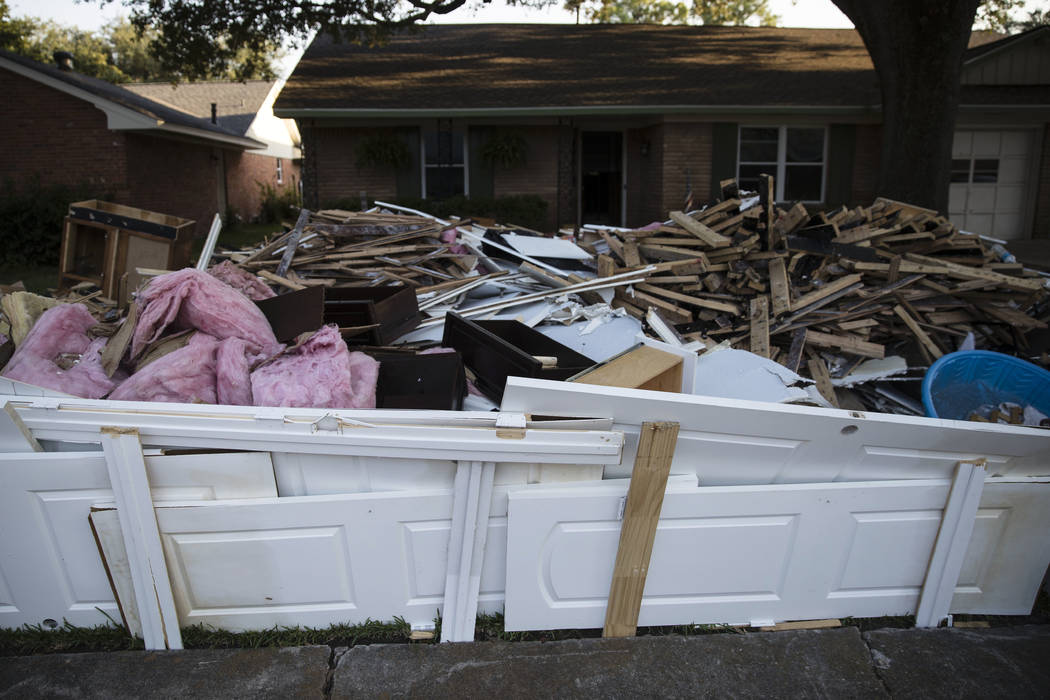 Debris sits in front of a home Wednesday in the aftermath of Hurricane Harvey in Houston. Harvey's record-setting rains now have the potential to set records for the amount of debris one storm can ...