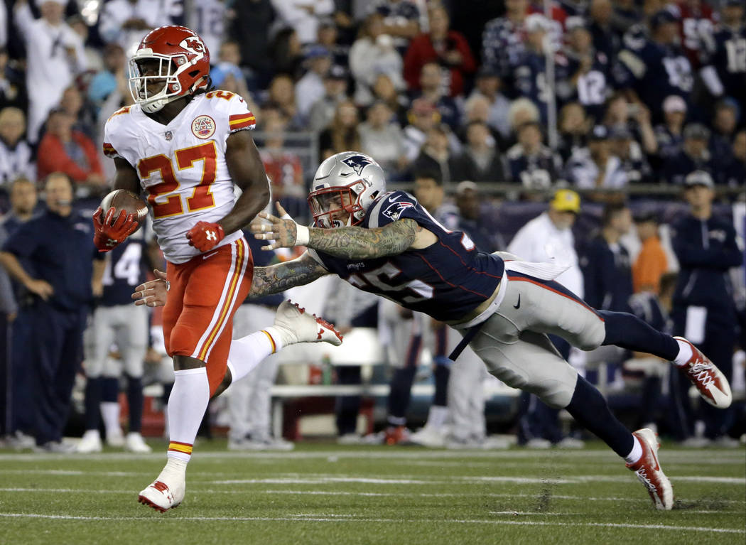 Kansas City Chiefs running back Kareem Hunt (27) eludes New England Patriots defensive end Cassius Marsh (55) as he runs for a touchdown after catching a pass from Alex Smith during the second hal ...