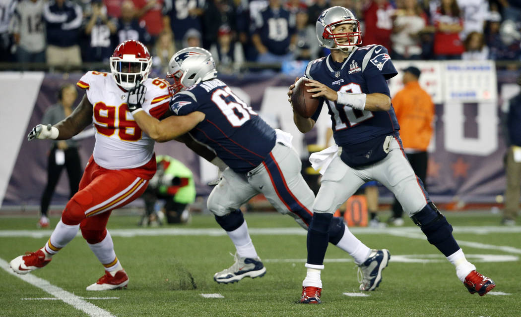 New England Patriots quarterback Tom Brady (12) drops back to pass as Kansas City Chiefs defensive tackle Bennie Logan (96) applies pressure during the second half of an NFL football game, Thursda ...