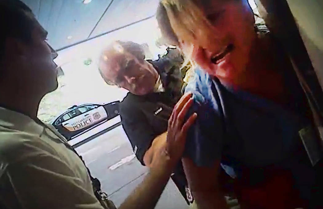 In this July 26, 2017, frame grab from video taken from a police body camera and provided by attorney Karra Porter, nurse Alex Wubbels is arrested by a Salt Lake City police officer at University  ...
