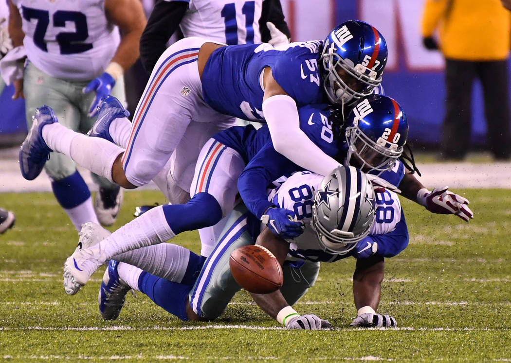 Dec 11, 2016; East Rutherford, NJ, USA;  Dallas Cowboys wide receiver Dez Bryant (88) fumbles the ball late in the fourth quarter as New York Giants cornerback Janoris Jenkins (20) makes the hit a ...