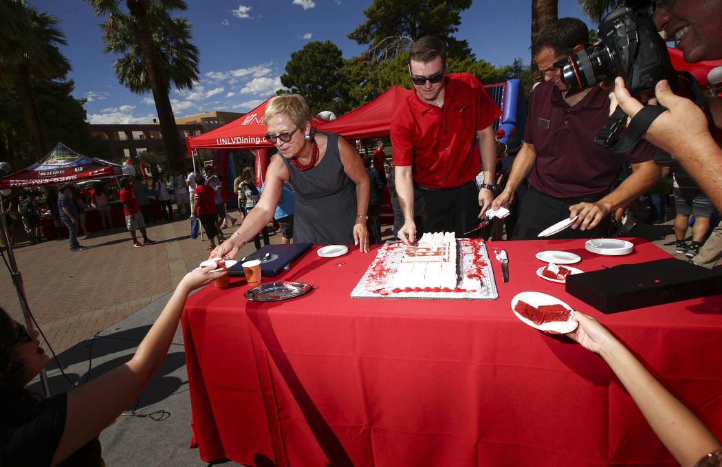 Diane Chase, executive vice president and provost at the school, left, hands out a piece of cake during an event marking UNLV's 60th birthday at Pida Plaza on the school's campus in Las Vegas on T ...