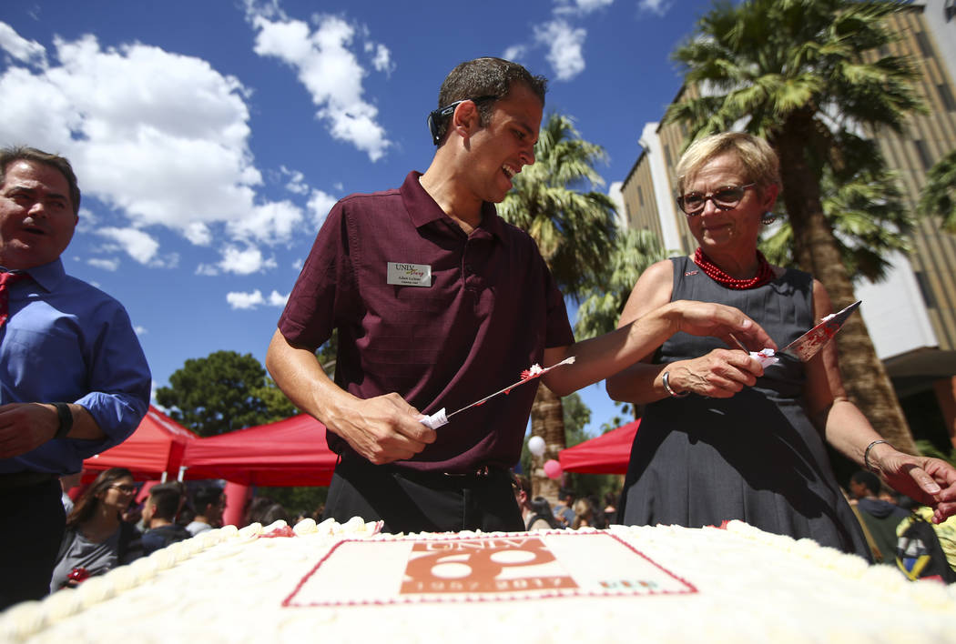 UNLV Dining catering lead Adam Leitner, center, and Diane Chase, executive vice president and provost at the school, cut pieces of cake during an event marking UNLV's 60th birthday at Pida Plaza o ...
