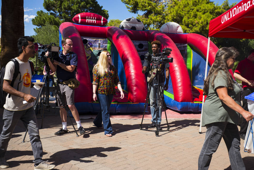 Students pass by news photographers during an event marking UNLV's 60th birthday at Pida Plaza on the school's campus in Las Vegas on Tuesday, Sept. 12, 2017. Chase Stevens Las Vegas Review-Journa ...