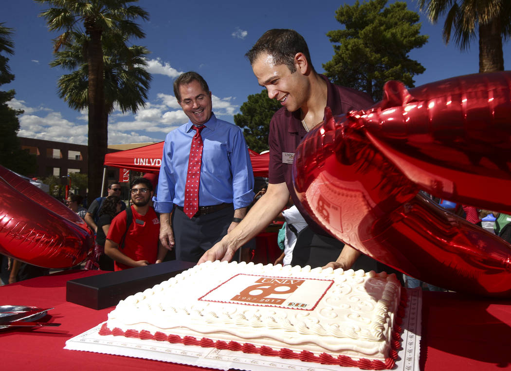 UNLV President Len Jessup, left, as UNLV Dining catering lead Adam Leitner places the cake during an event marking UNLV's 60th birthday at Pida Plaza on the school's campus in Las Vegas on Tuesday ...
