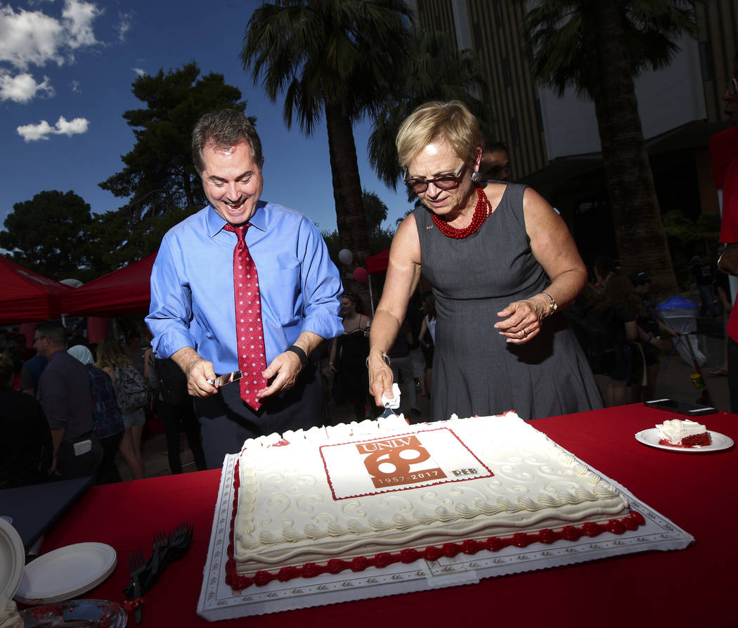 UNLV President Len Jessup, left, and Diane Chase, executive vice president and provost at the school, cut pieces of cake during an event marking UNLV's 60th birthday at Pida Plaza on the school's  ...