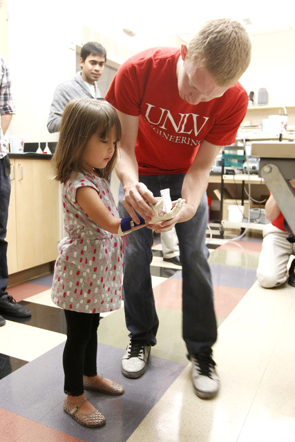 Mechanical engineering student Zachary Cook helps Hailey Dawson try on her new prosthetic hand, which was made by a team of UNLV engineers, Thursday, Oct. 30, 2014 at UNLV. (Sam Morris/Las Vegas R ...
