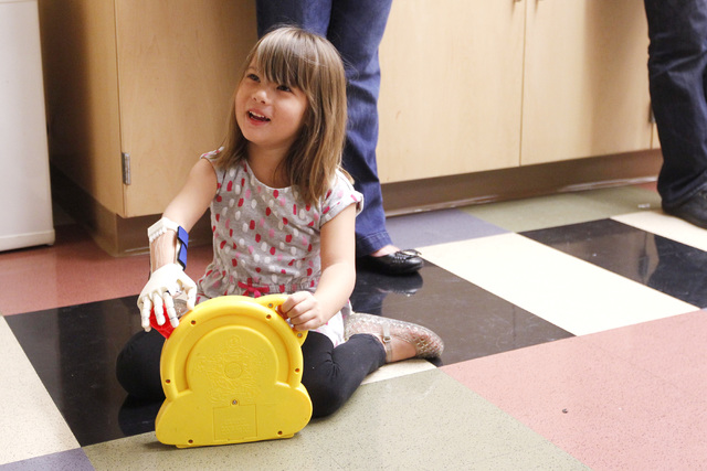 Hailey Dawson uses her new prosthetic hand to play with a See 'N Say toy Thursday, Oct. 30, 2014 at UNLV. (Sam Morris/Las Vegas Review-Journal)