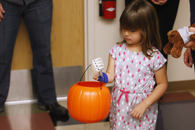 Hailey Dawson carries a trick or treat pumpkin with her new prosthetic hand Thursday, Oct. 30, 2014 at UNLV. (Sam Morris/Las Vegas Review-Journal)