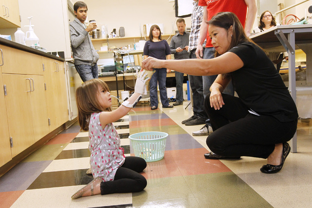 Occupational therapist Cynthia Lau hands a bean bag to Hailey Dawson to test her new prosthetic hand Thursday, Oct. 30, 2014 at UNLV. (Sam Morris/Las Vegas Review-Journal)