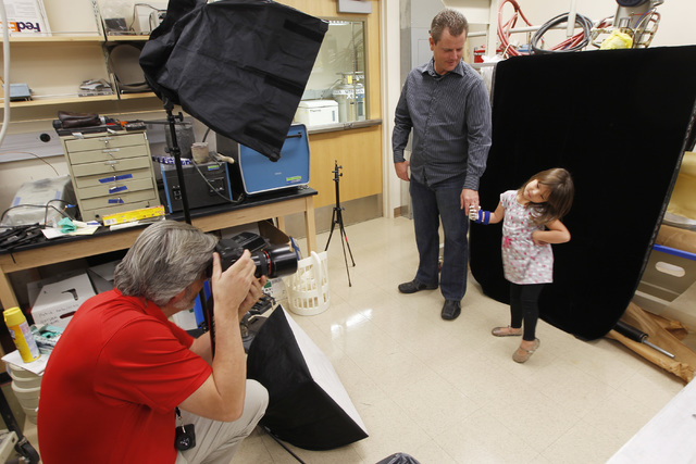 UNLV Photo Services photographer Aaron Mayes takes a photo of Greg Dawson and Hailey Dawson after Hailey was fitted with her new prosthetic hand Thursday, Oct. 30, 2014 at UNLV. (Sam Morris/Las Ve ...