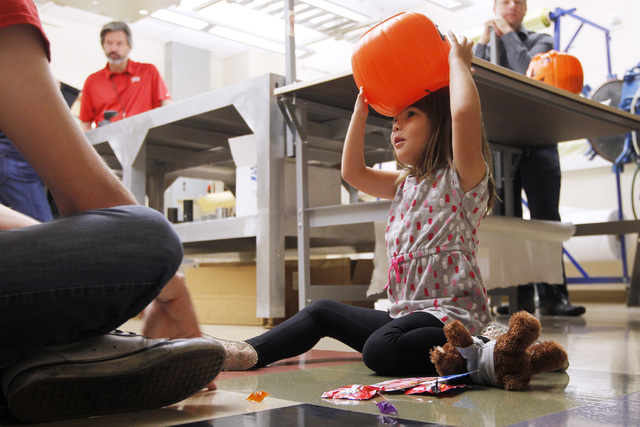 Hailey Dawson puts a trick or treat pumpkin on her head while waiting to be fitted with her new prosthetic hand Thursday, Oct. 30, 2014 at UNLV. (Sam Morris/Las Vegas Review-Journal)