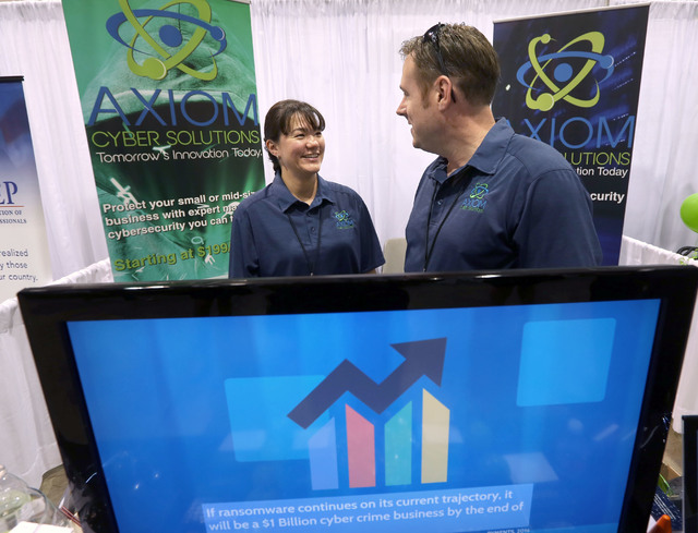 Axiom Cyber Solutions president Shannon Wilkinson, left, and her husband CEO Troy Wilkinson talks during the Business Expo sponsored by Las Vegas Metro Chamber at Cashman Field on Wednesday, June  ...