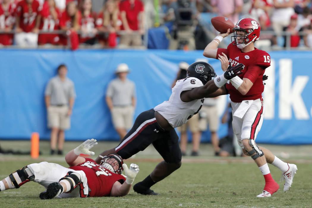 North Carolina State's Ryan Finley (15) gets his pass away as South Carolina's Keir Thomas (5) beats North Carolina State's Justin Witt (67) during the second half of an NCAA football game in Char ...