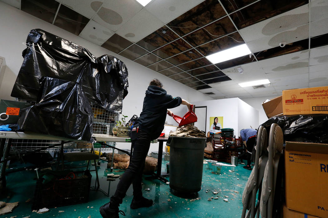 Thai restaurant Lotus of Siam staff members Brittany Edberg, left, and Sabrina Chutima removes debris after a portion of its ceiling collapsed in Las Vegas, Friday, Sept. 8, 2017. Chitose Suzuki L ...