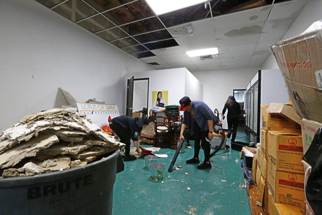 Thai restaurant Lotus of Siam staff members Brittany Edberg, left, and Sabrina Chutima, center, removes debris after a portion of its ceiling collapsed in Las Vegas, Friday, Sept. 8, 2017. Chitose ...
