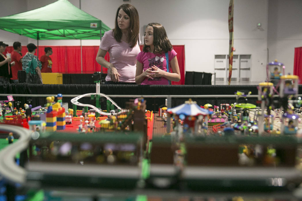 Stephanie Anderson, left, and daughter Makayla Anderson, 9, both of Henderson, admire Suzy Lentchner and Lance Paulson's LEGO State Fair display during Brick Fest Live! at the Las Vegas Convention ...