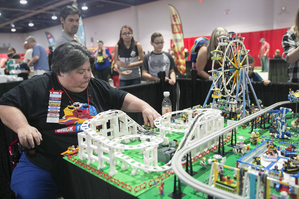 "Suzy Lentchner, from Ontario, Calif., a self-described ""LEGO artist"", fixes the roller coaster on her and Lance Paulson's LEGO State Fair display during Brick Fest Live! at the L ..."