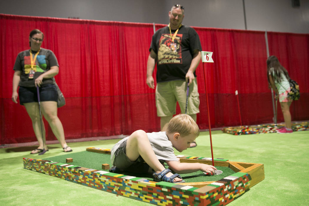 Ethan Schroth, 3, center, plays mini golf while his parents, Christine Schroth and Matthew Schroth look on during Brick Fest Live! at the Las Vegas Convention Center in Las Vegas on Saturday, Sept ...