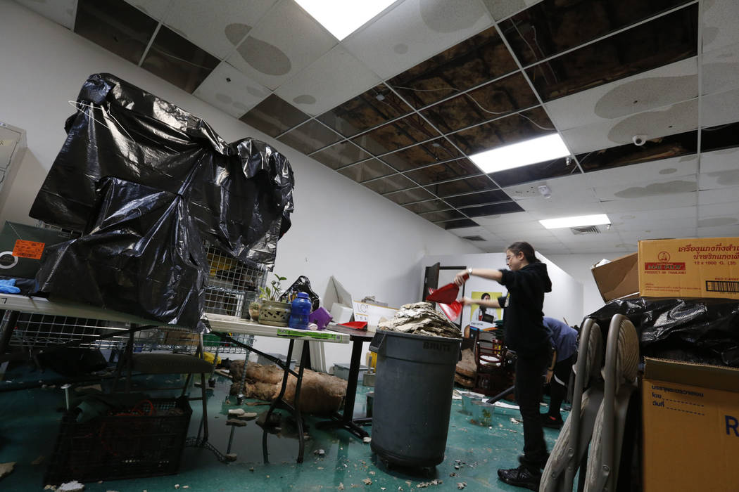 Thai restaurant Lotus of Siam staff members Brittany Edberg, center and Sabrina Chutima, behind, removes debris after a portion of its ceiling collapsed in Las Vegas, Friday, Sept. 8, 2017. Chitos ...