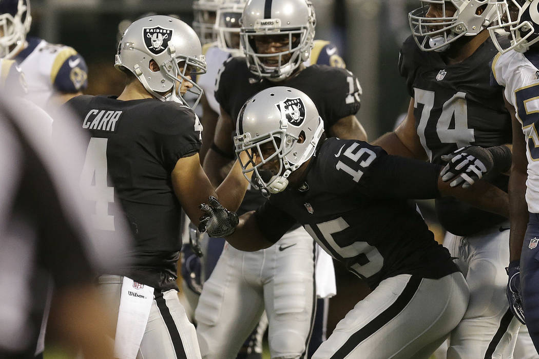 Oakland Raiders quarterback Derek Carr and wide receiver Michael Crabtree celebrate after connecting on a touchdown pass against the Los Angeles Rams during the first half of an NFL prese