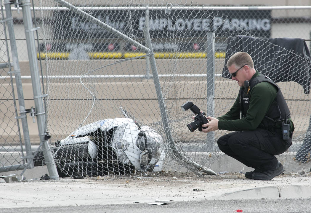 A crime scene photographer at he scene of an accident where a man died after crashing his motorcycle into fence near the intersection of Dean Martin Drive and West Tropicana Avenue on Saturday, Se ...