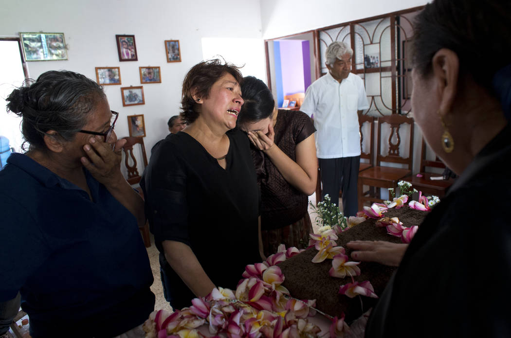 Family members grieve over the coffin containing the remains of 64-year-old Reynalda Matus during a wake, in Juchitan, Oaxaca state, Mexico, Saturday, Sept. 9, 2017. Matus was killed when the phar ...