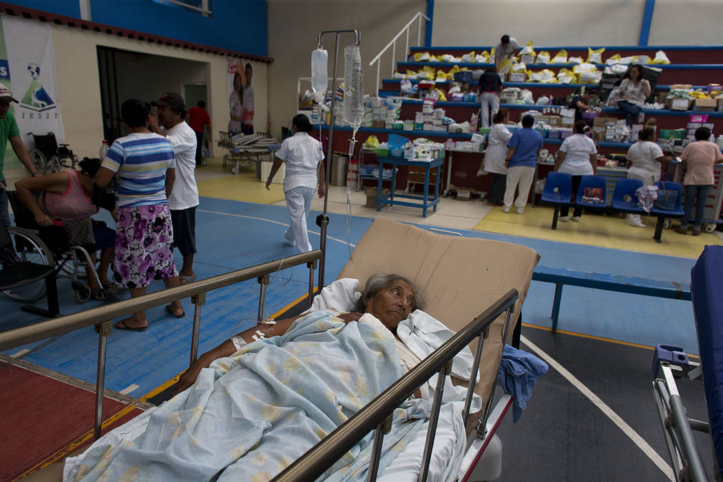 A 71-year-old woman, who was injured when a wall collapsed on her in Thursday's massive earthquake, receives treatment in a medical ward set up on a school's basketball court, in Juchitan, Oaxaca  ...
