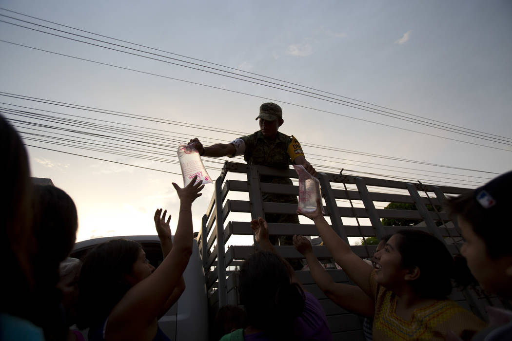 Soldiers hand out bags of water to people in zones heavily affected by Thursday's massive earthquake, in Juchitan, Oaxaca state, Mexico, Saturday, Sept. 9, 2017. A magnitude 8.1 earthquake struck  ...