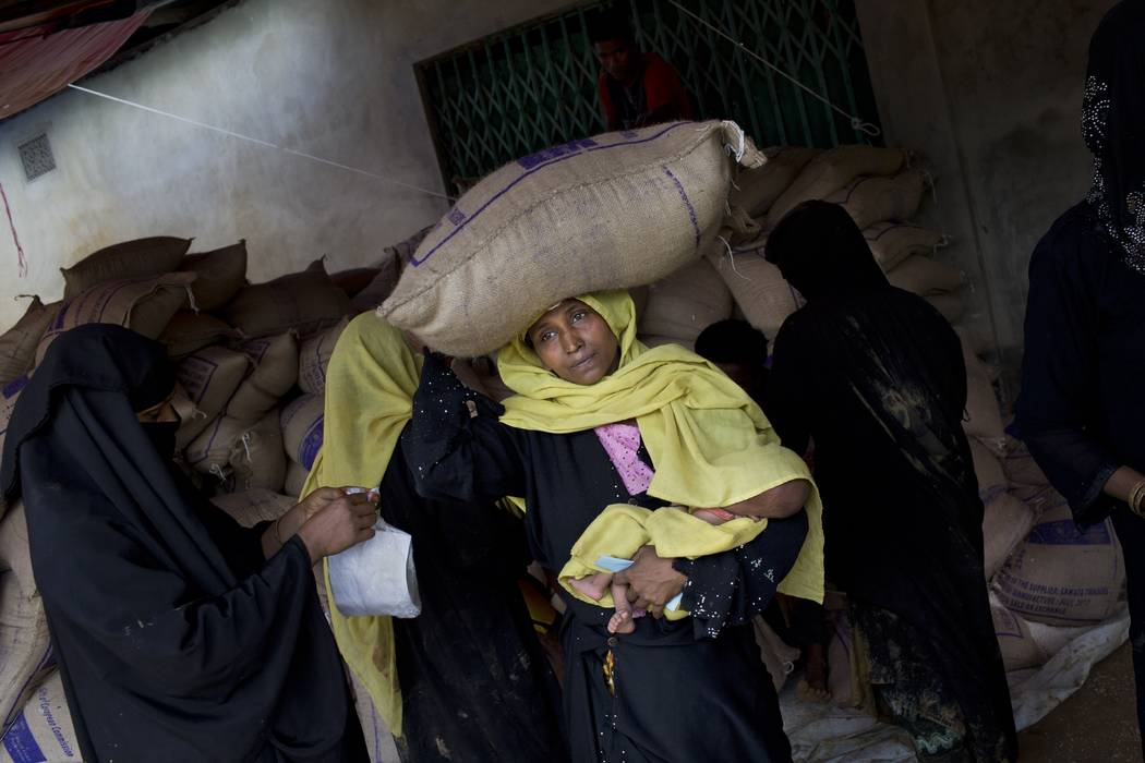 A Rohingya Muslim woman, who recently crossed the border from Myanmar into Bangladesh, carries a 25 kilogram bag of rice, distributed by aid agencies, on her head while also holding an infant chil ...