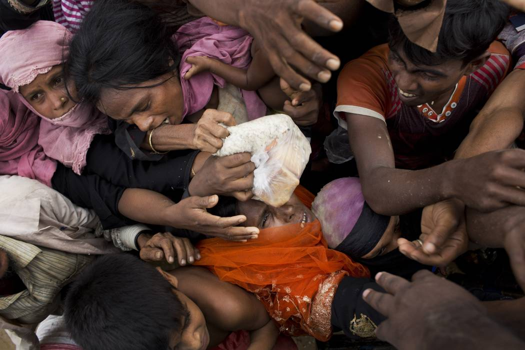 Rohingya Muslims, newly arrived from Myanmar, scuffle for puffed rice food rations donated by local volunteers in Kutupalong, Bangladesh, Saturday, Sept. 9, 2017. With Rohingya refugees still floo ...