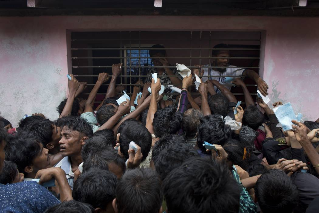 Newly arrived Rohingya try to get their tokens validated in order to collect a bag of rice distributed by aid agencies in Kutupalong, Bangladesh, Saturday, Sept. 9, 2017. Many of the newly arrived ...