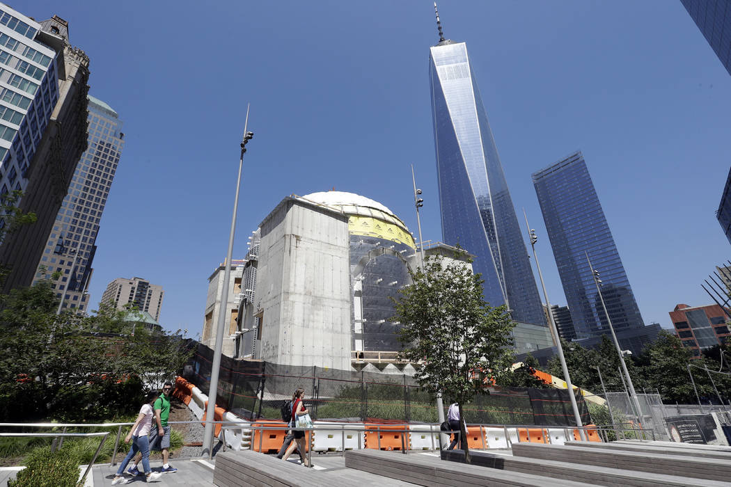 In this Aug. 10, 2017 photo, the St. Nicholas National Shrine, center, designed by renowned architect Santiago Calatrava, is under construction at the World Trade Center in New York. It is replaci ...