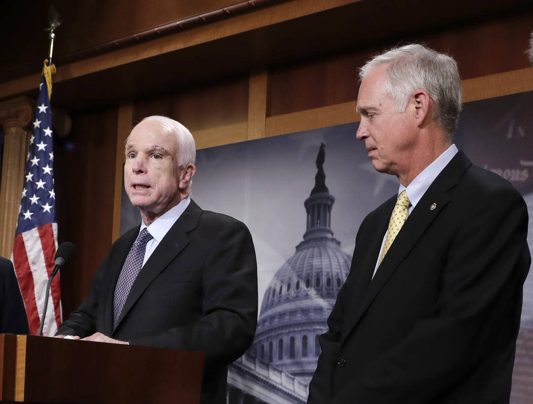 In this July 27, 2017 file photo, Sen. Ron Johnson, R-Wis. listens as Sen. John McCain, R-Ariz. speaks on Capitol Hill in Washington.  Johnson suggested that John McCain's brain tumor and the afte ...