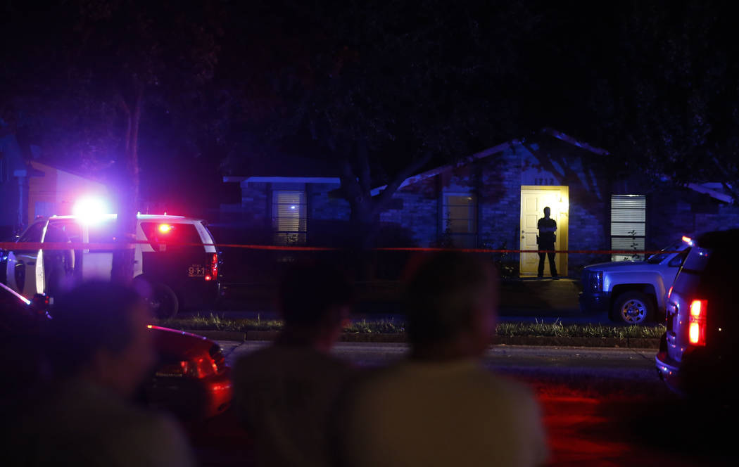 Onlookers watch police work the scene of a shooting at a home in Plano, north of Dallas, Texas, Sunday night, Sept. 10, 2017. Authorities in North Texas say several people are dead, including the  ...