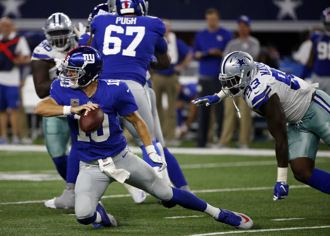 New York Giants quarterback Eli Manning (10) attempts to get rid of the ball under pressure from Dallas Cowboys defensive end Benson Mayowa (93) in the second half of an NFL football game, Sunday, ...