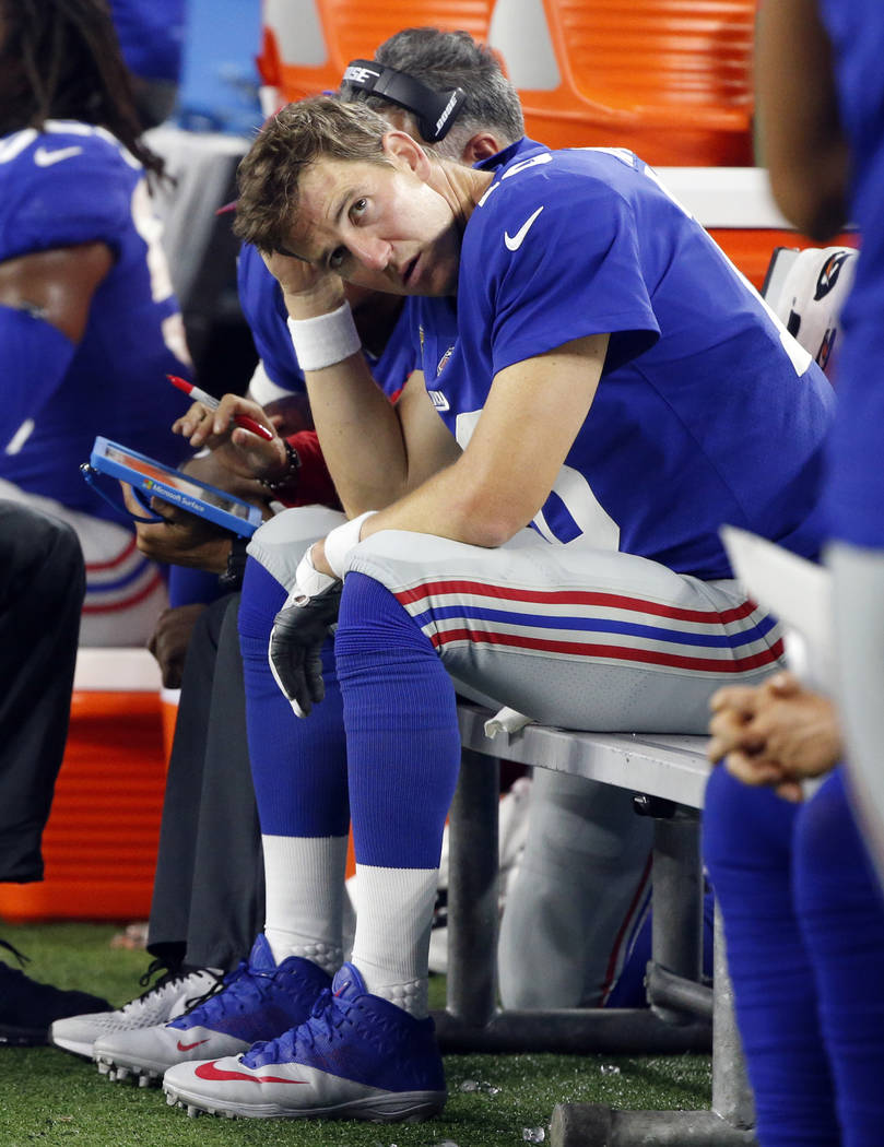 New York Giants quarterback Eli Manning sits on the sideline in the first half of an NFL football game against the Dallas Cowboys on Sunday, Sept. 10, 2017, in Arlington, Texas. (AP Photo/Michael  ...