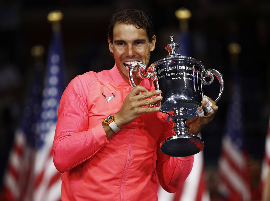 Rafael Nadal, of Spain, holds up the championship trophy after beating Kevin Anderson, of South Africa, in the men's singles final of the U.S. Open tennis tournament, Sunday, Sept. 10, 2017, in Ne ...