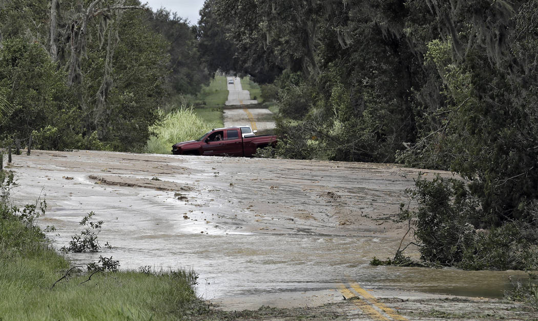 Motorists turn around after a levee from a phosphate plant ruptured from rain and wind associated with Hurricane Irma on Monday, Sept. 11, 2017, in Homeland, Fla. (AP Photo/Chris O'Meara)