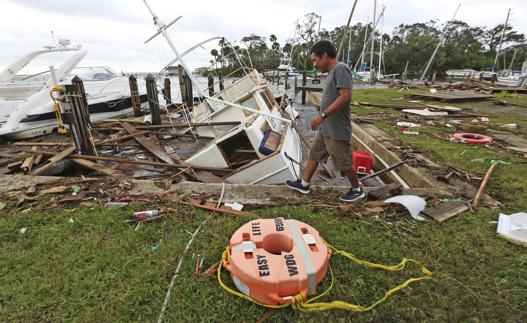 A man walks by damage from Hurricane Irma at Sundance Marine in Palm Shores, Fla., Monday, Sept. 11, 2017 (Red Huber/Orlando Sentinel via AP)