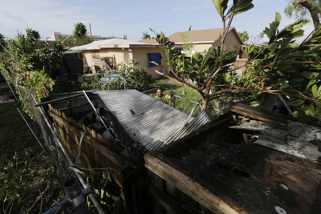 Bayardo Perez prepares to dismantle the mangled tin roof of his shed in Sweetwater, Fla., Monday, Sept. 11. Inland communities like Sweetwater were spared the storm surge from Hurricane Irma, but  ...