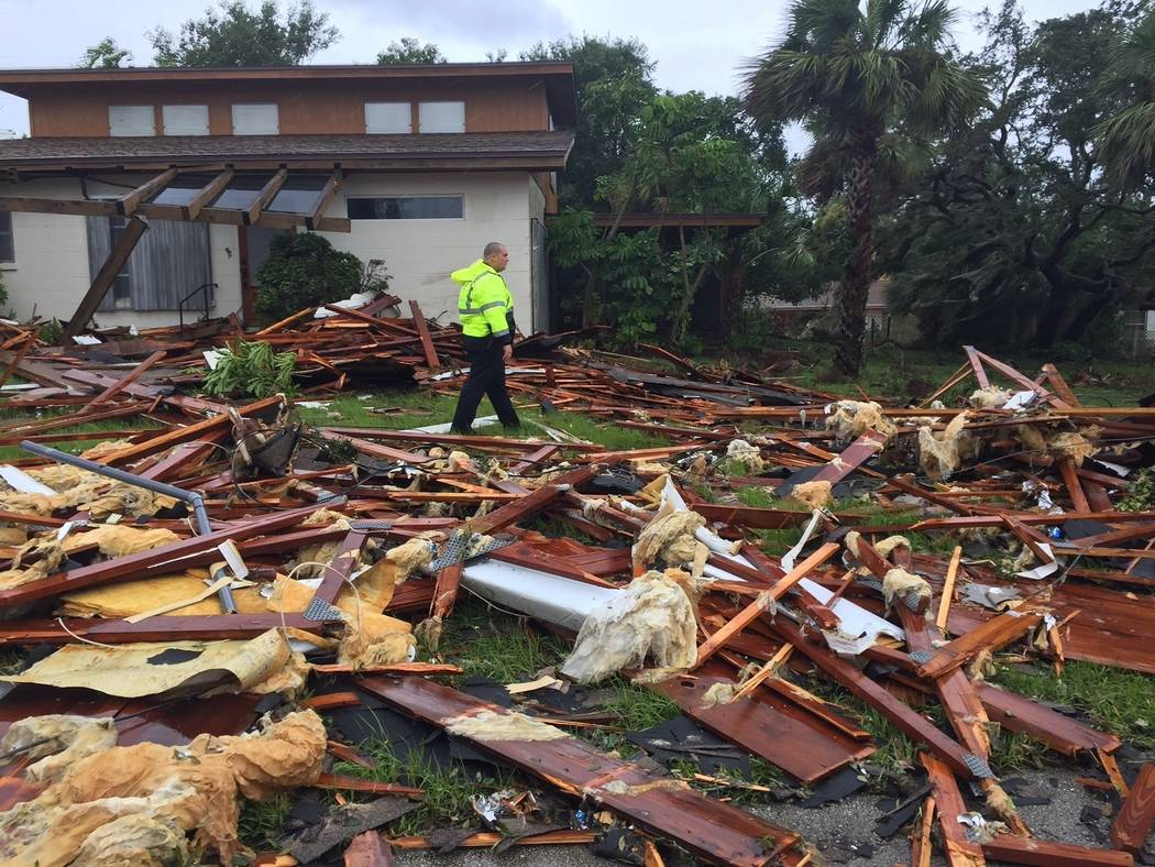 Palm Bay officer Dustin Terkoski walks over debris from a two-story home at Palm Point Subdivision in Brevard County, Fla., after a tornado touched down on Sunday, Sept. 10, 2017. (Red Huber/Orlan ...
