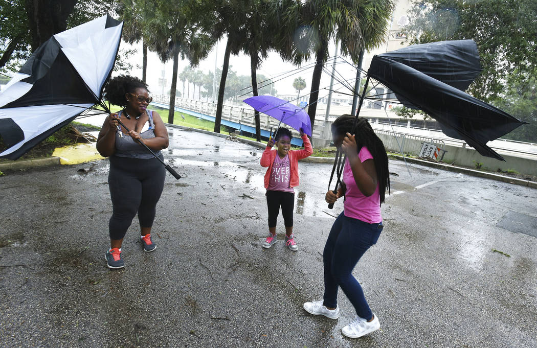 Umbrellas held by Janesse Brown, left, and her daughter Briana Johnson, 12, right, get torn apart by strong winds as Kyra Johnson, 8 watch, while they tried to visit Southbank Riverwalk in Jackson ...