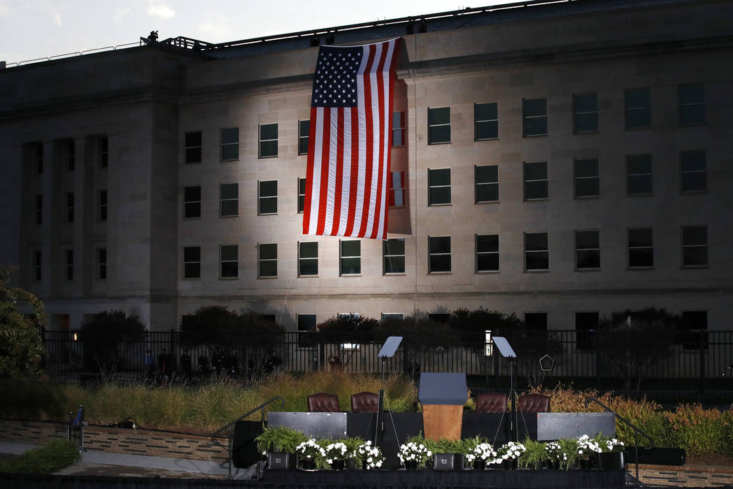 The podium awaits the arrival of President Donald Trump as a U.S. flag is unfurled at the Pentagon on the 16th anniversary of the September 11th attacks Monday, Sept. 11, 2017. (AP Photo/Jacquelyn ...