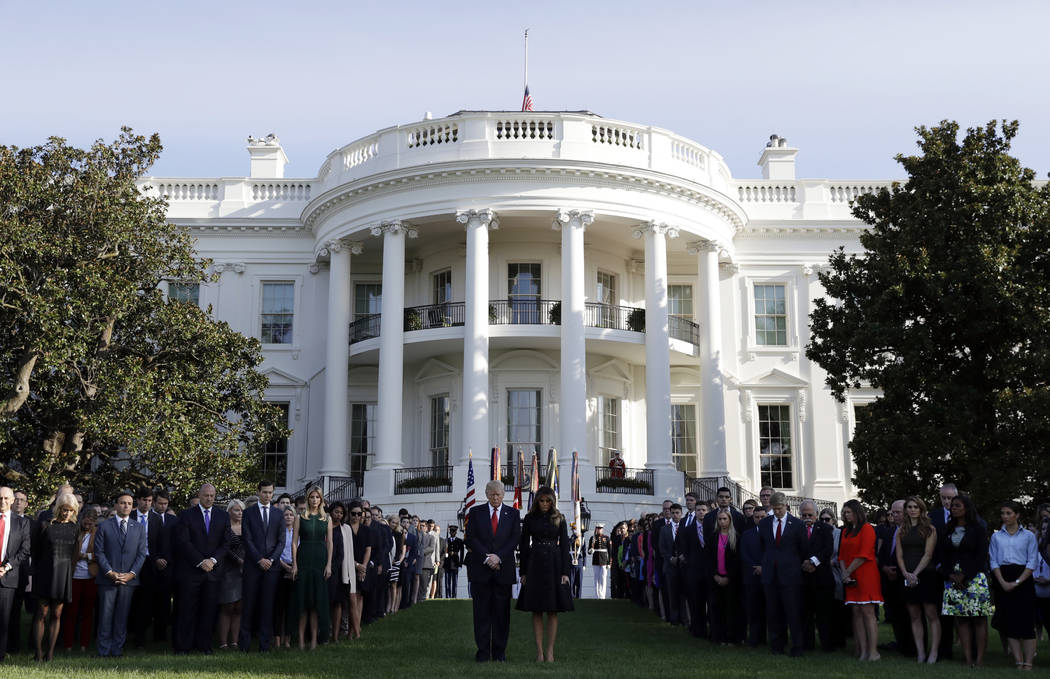 President Donald Trump and first lady Melania Trump stand for a moment of silence to mark the anniversary of the Sept. 11 terrorist attacks, on the South Lawn of the White House, Monday, Sept. 11, ...