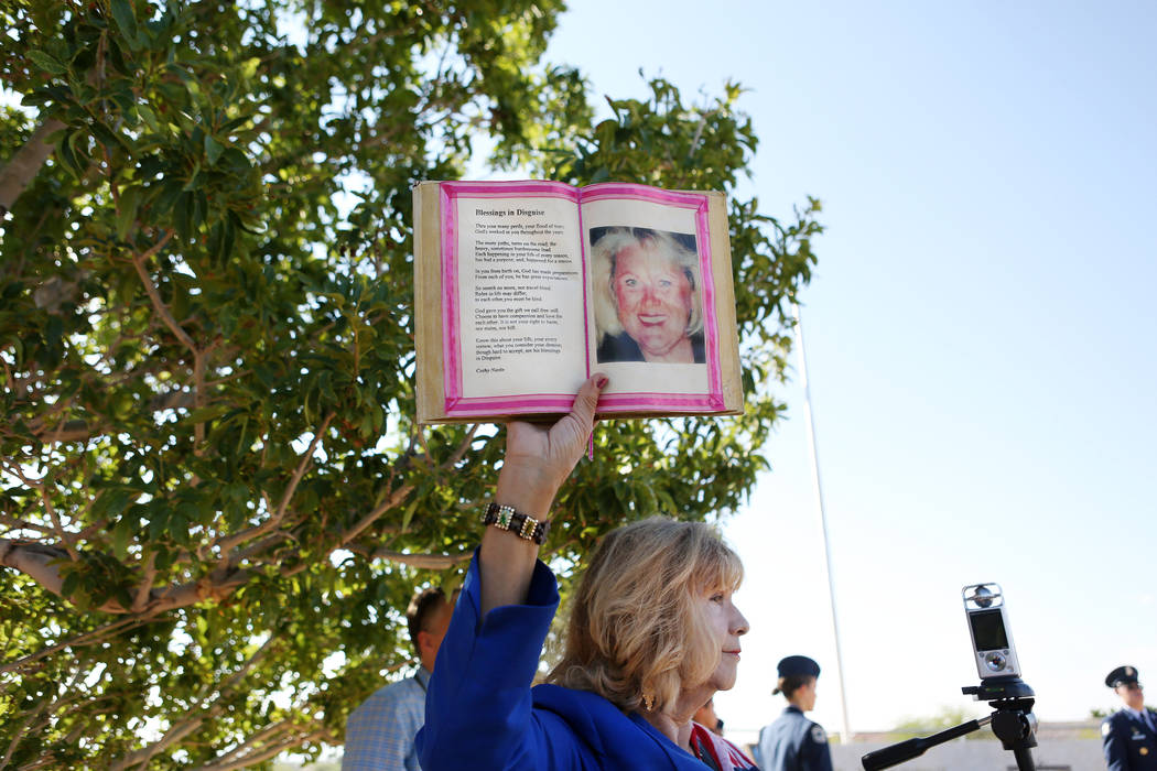 Poet and co-founder of My Angel Cafe, Cathy Navin, holds a poem and photo of Barbra Edwards during Palo Verde High School's Air Force JROTC's annual rededication ceremony in remembrance of the vic ...