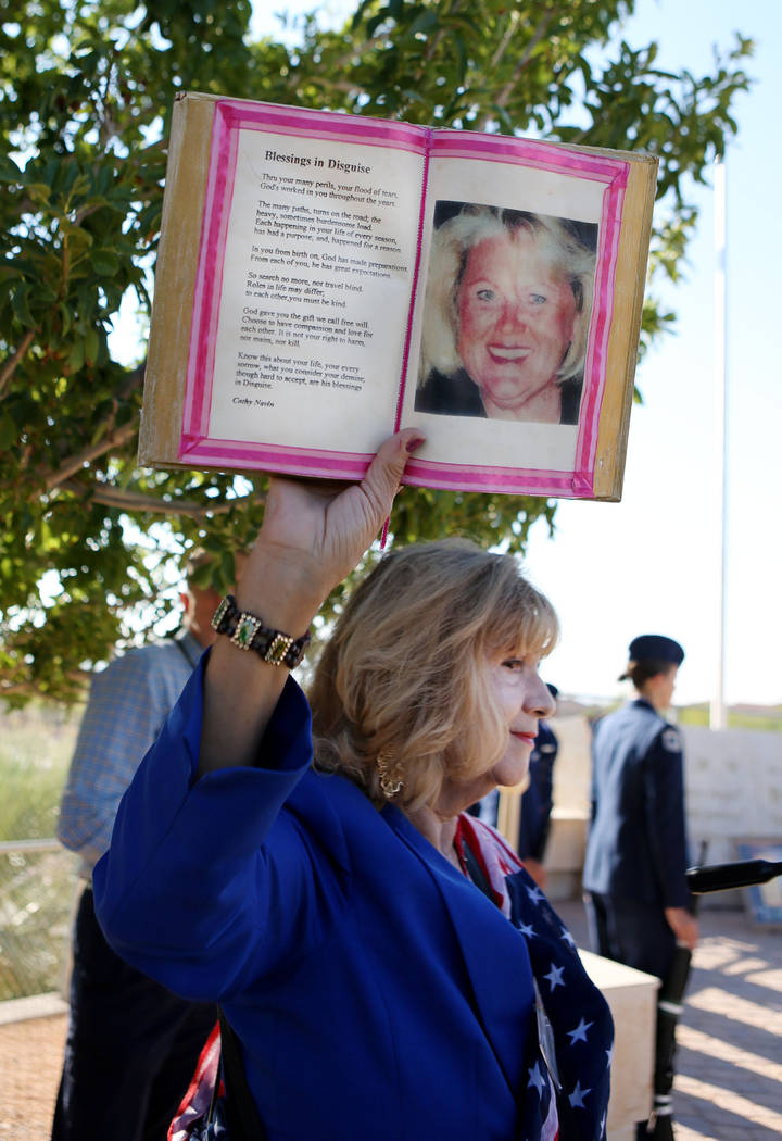 Poet and co-founder of My Angel Cafe Cathy Navin holds a poem and photo of Barbra Edwards during Palo Verde High School's Air Force JROTC's annual rededication ceremony in remembrance of the victi ...